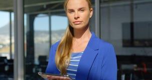 Mulher de negócios caucasiano com posição digital da tabuleta no escritório moderno 4k vídeos de arquivo
