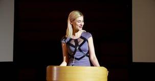Mulher de negócios caucasiano loura nova que fala no seminário do negócio no auditório 4k vídeos de arquivo