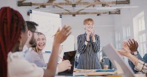 Mulher de negócios caucasiano nova bonita do CEO que dá um discurso da motivação à equipe multi-étnico feliz na reunião do video estoque