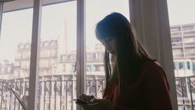 Mulher de negócios caucasiano nova bonita feliz que usa o computador e o smartphone na grande janela do apartamento no verão Pari video estoque