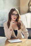 Mulher de negócios caucasiano nova com caderno Mulher nos vidros em um café Fotografia de Stock Royalty Free