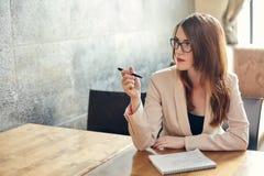 Mulher de negócios caucasiano nova com caderno Mulher nos vidros em um café Fotografia de Stock