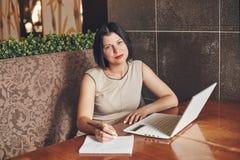 Mulher de negócios caucasiano nova com portátil e caderno Mulher no café Imagens de Stock Royalty Free