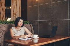 Mulher de negócios caucasiano nova com portátil e caderno Mulher no café Imagem de Stock