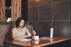 Mulher de negócios caucasiano nova com portátil e caderno Mulher no café Fotografia de Stock