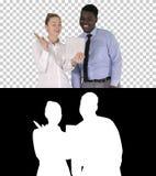 Mulher de negócios caucasiano nova e seu colega africano que fazem a chamada video com tabuleta, Alpha Channel fotografia de stock