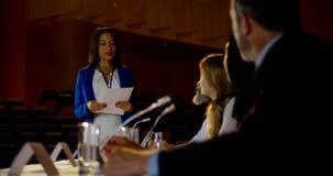 Mulher de negócios caucasiano nova que fala com os colegas na fase no auditório 4k vídeos de arquivo