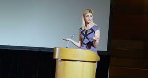 Mulher de negócios caucasiano nova que fala na fase no auditório 4k video estoque