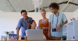 A mulher de negócios caucasiano que trabalha em seu portátil está interagindo com a outro executivos em um escritório vídeos de arquivo