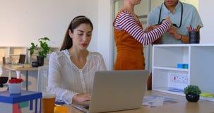 Mulher de negócios caucasiano que trabalha no portátil na mesa no escritório moderno 4k video estoque