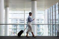 Mulher de negócios caucasiano que usa o telefone celular ao andar no escritório fotografia de stock