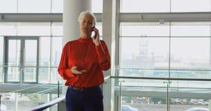 Mulher de negócios caucasiano superior que fala no telefone celular no escritório 4k video estoque