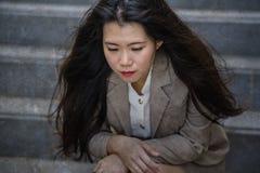 Mulher de negócios chinesa asiática deprimida e desesperada que grita apenas sentando-se no esforço e na depressão do sofrimento  fotografia de stock royalty free