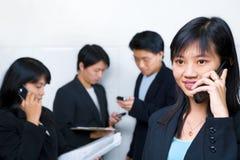 Mulher de negócios chinesa nova que fala no telefone de pilha Fotografia de Stock Royalty Free