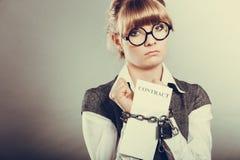 Mulher de negócios com as mãos acorrentadas que guardam o contrato Fotos de Stock