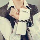 Mulher de negócios com as mãos acorrentadas que guardam o contrato Imagens de Stock Royalty Free