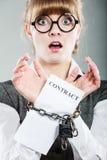 Mulher de negócios com as mãos acorrentadas que guardam o contrato Foto de Stock