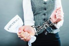 Mulher de negócios com as mãos acorrentadas que guardam o contrato Fotografia de Stock