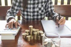 A mulher de negócios com a calculadora que conta fazendo anotações, mão é wri imagens de stock