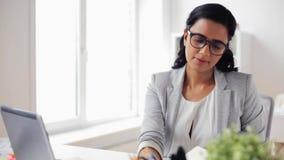 Mulher de negócios com a calculadora que conta no escritório vídeos de arquivo