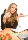 Mulher de negócios com chaves e casa do brinquedo no escritório Foto de Stock