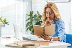 Mulher de negócios com diário e portátil fotografia de stock