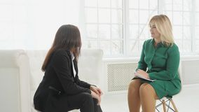 A mulher de negócios com divisão nervosa fala ao psicólogo que toma notas