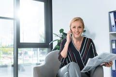 Mulher de negócios com jornal que fala pelo telefone foto de stock royalty free