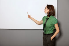 Mulher de negócios com mãos em uns bolsos que aponta no whiteboard no escritório Fotografia de Stock Royalty Free