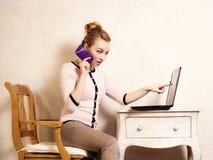 Mulher de negócios com o portátil da tela tocante do telefone Fotografia de Stock Royalty Free