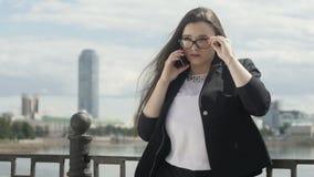 Mulher de negócios com o smartphone na rua filme