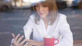 Mulher de negócios com o smartphone que senta-se no café na frente da parede de vidro vídeos de arquivo