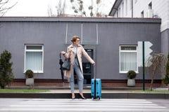 mulher de negócios com o táxi de espera da mala de viagem e do guarda-chuva foto de stock royalty free