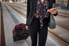 Mulher de negócios com sacos usando seu telefone celular em uma parada do bonde foto de stock