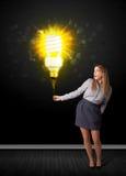 Mulher de negócios com um bulbo eco-amigável Fotografia de Stock