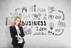 Mulher de negócios com um caderno que está perto de um muro de cimento com ícones da ideia do negócio fotografia de stock royalty free