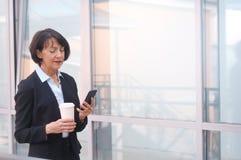 Mulher de negócios com um smartphone e uma xícara de café fotografia de stock