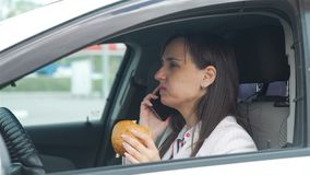 Mulher de negócios com um telefone que tem o almoço em um carro vídeos de arquivo