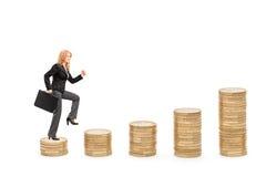 Mulher de negócios com uma pasta que anda sobre pilhas das moedas Imagem de Stock