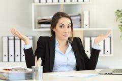 Mulher de negócios confusa que olha a câmera imagem de stock