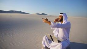 Mulher de negócios considerável do indivíduo do xeique dos UAE do Arabian que chama o sócio comercial que senta-se na areia com o vídeos de arquivo