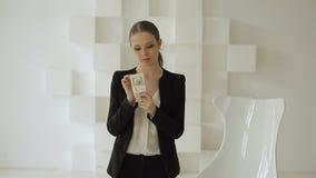 Mulher de negócios consideravelmente bonita no terno formal que recebe a pilha de dinheiro filme