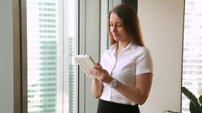 Mulher de negócios consideravelmente nova que está na janela do escritório usando a tabuleta video estoque