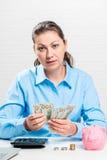 A mulher de negócios da mulher de negócios conta dólares, perto dela um pigg cor-de-rosa Foto de Stock