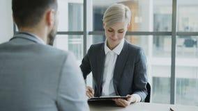 Mulher de negócios da hora que tem a entrevista de trabalho com o homem novo no terno e que olha sua aplicação do resumo no escri