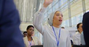 mulher de negócios da Misturado-raça que levanta a mão no seminário 4k do negócio vídeos de arquivo