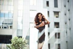 A mulher de negócios da raça consideravelmente misturada fala pelo telefone na cidade fotos de stock royalty free