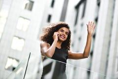 A mulher de negócios da raça consideravelmente misturada fala pelo telefone na cidade fotografia de stock