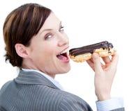 Mulher de negócios de incandescência que come um eclair de chocolate foto de stock