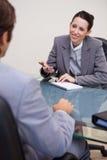 Mulher de negócios de sorriso com o bloco de notas na negociação Fotografia de Stock Royalty Free